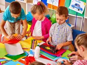 Kids holding colored paper on table in kindergarten